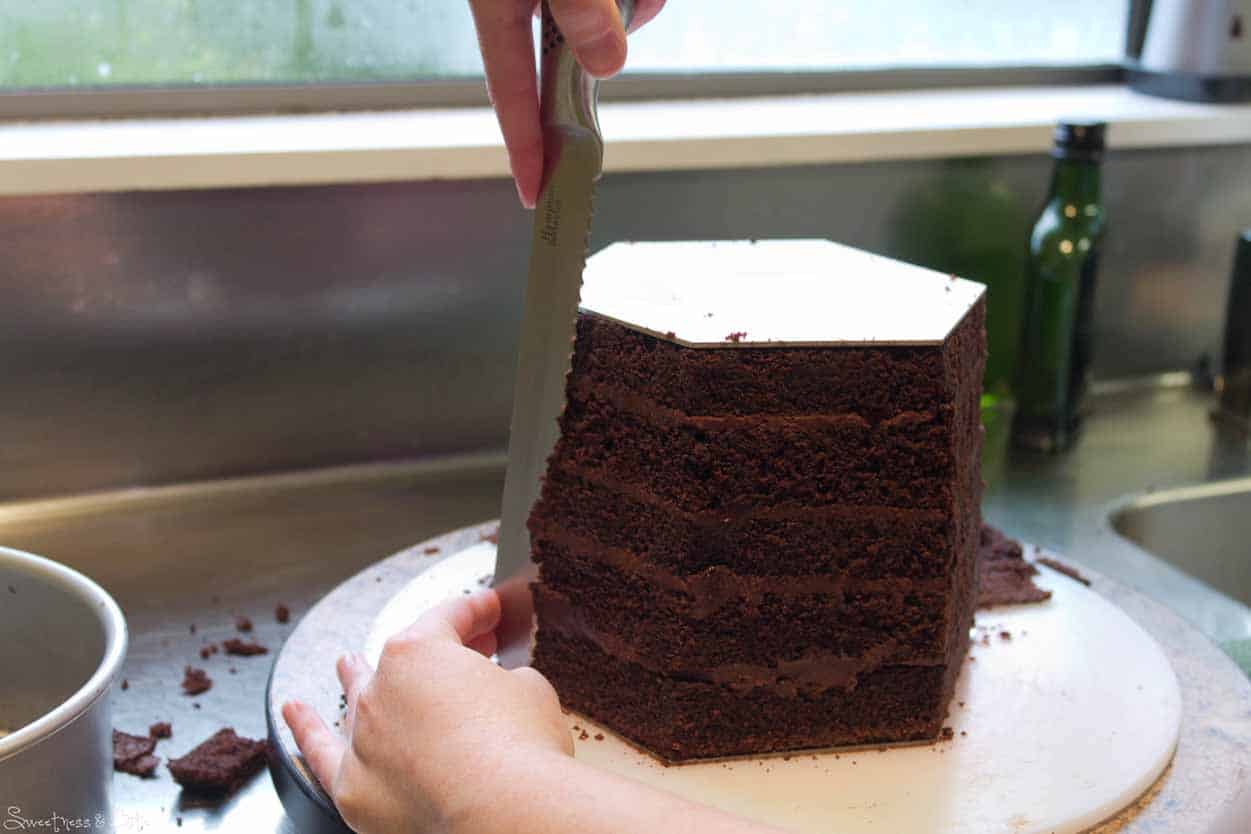 This is why you don't want a flexible knife. Press the knife against both boards to shave away the cake.