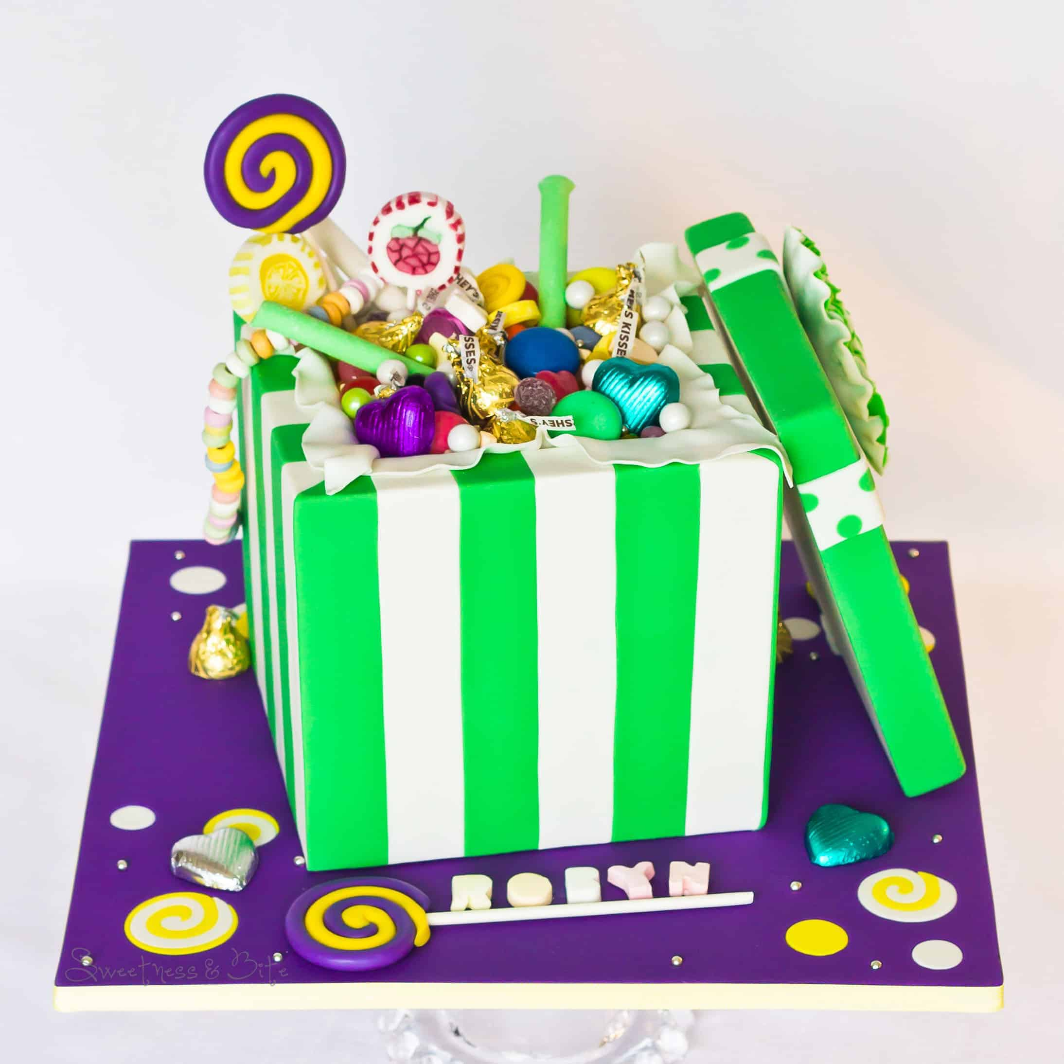 Cake filled with Jelly beans, chocolate hearts, Hershey's kisses, jelly hearts, fizzy letters, fruit tingles, tiny jubes, giant smarties, green and white sixlets, candy necklace, spearmint pencils, lolly pops, and handmade modelling chocolate 'lolly pops""