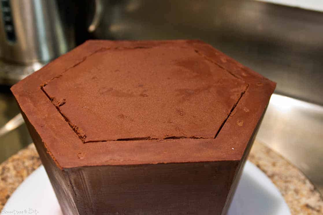 Start removing the middle, the ganache will probably come off first, then carefully pry out the cake.