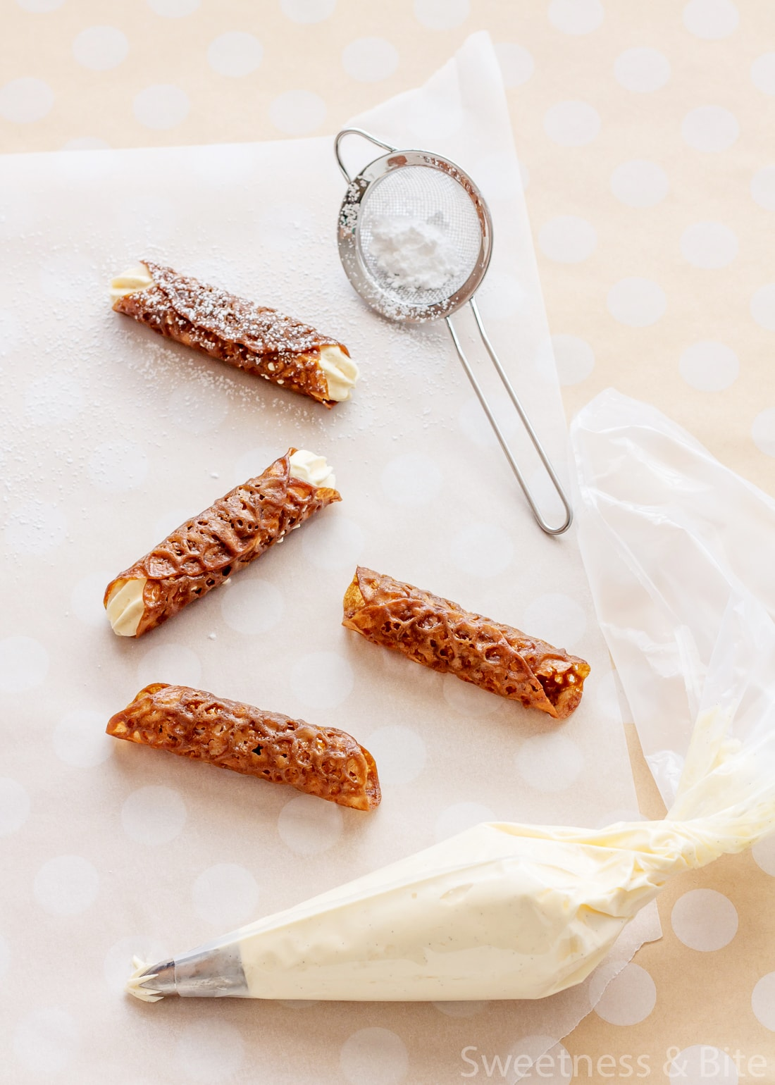 Four brandy snaps on a piece of baking paper, with a small sieve holding icing sugar.