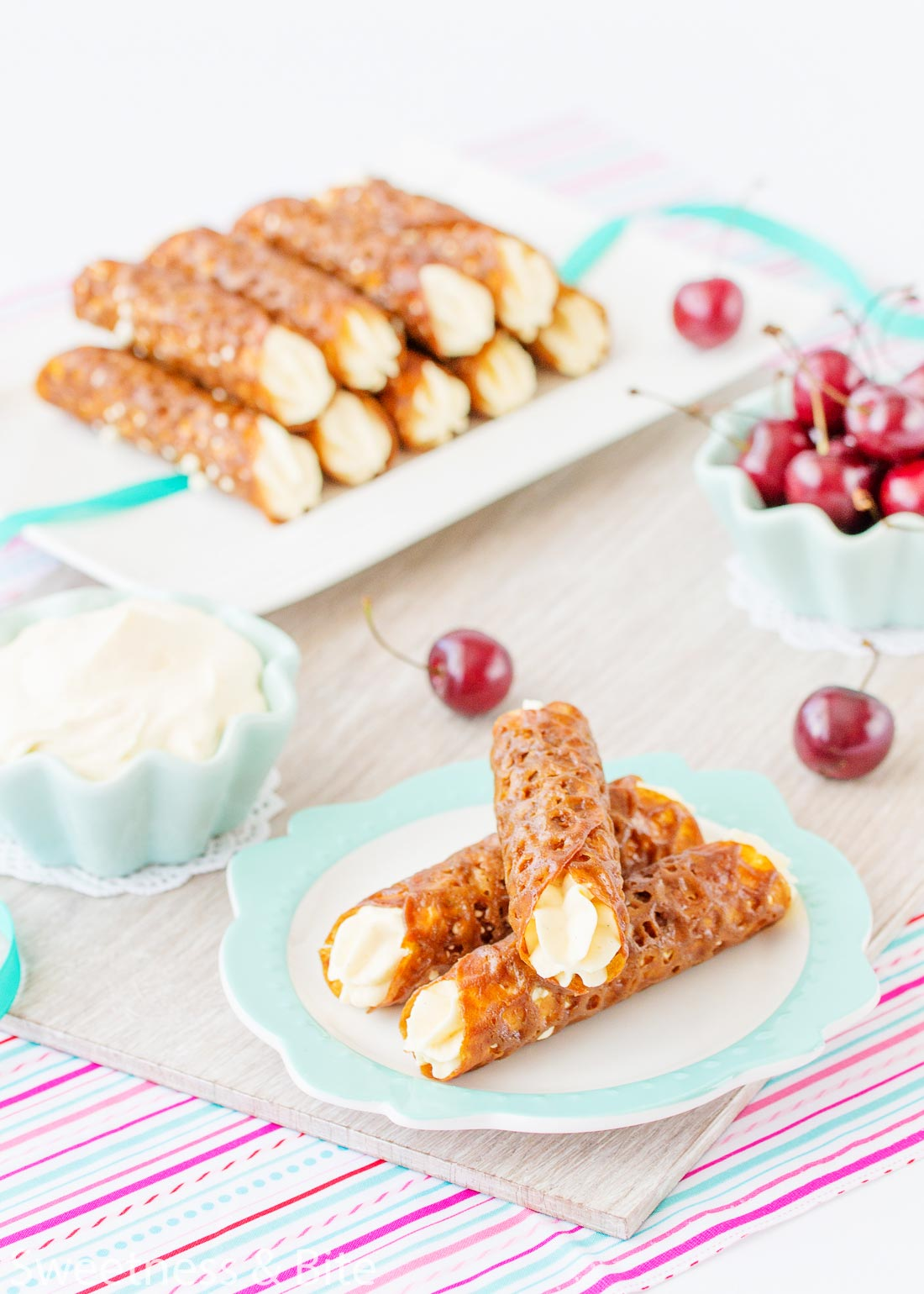 Three gluten free brandy snaps stacked on a plate in the foreground, with a bowl of whipped cream and fresh cherries in the background.