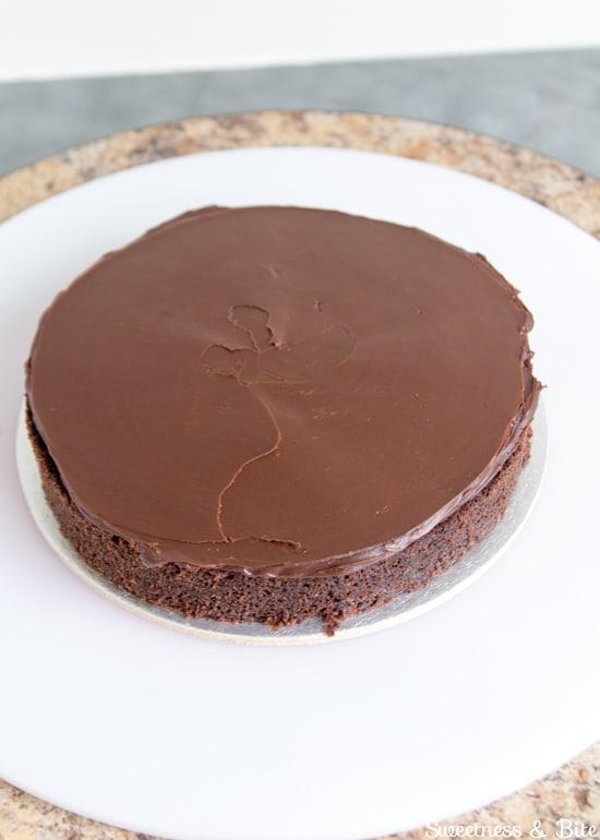One cake layer spread with dark chocolate ganache.