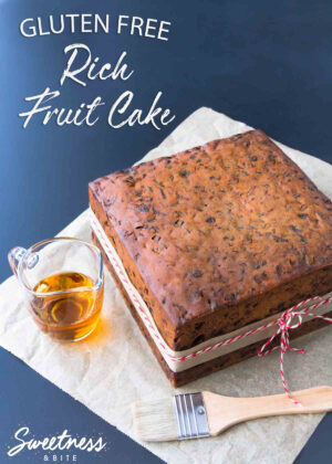A square gluten free rich fruit cake on a piece of parchment paper, with a small glass jug of brandy and a pastry brush