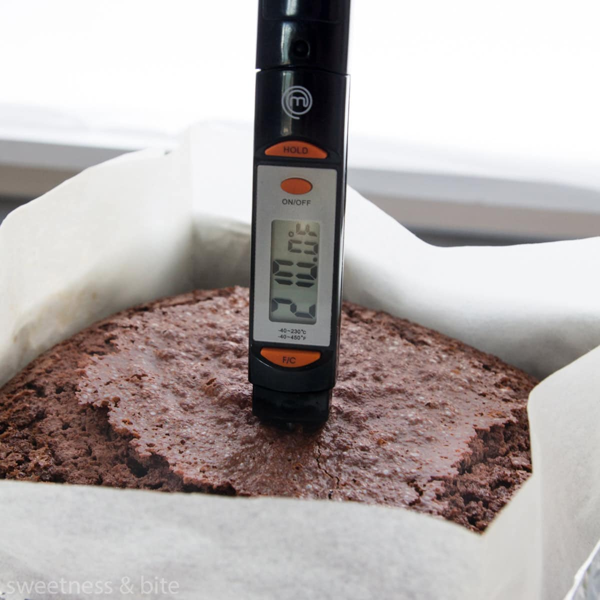 A thermometer being used to check the internal temperature of a cake in Fahrenheit.