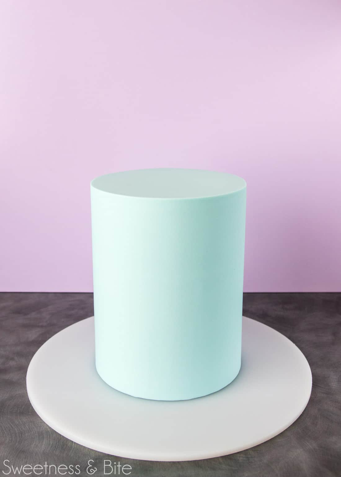 Tall, pale blue fondant covered cake, ready to be painted.