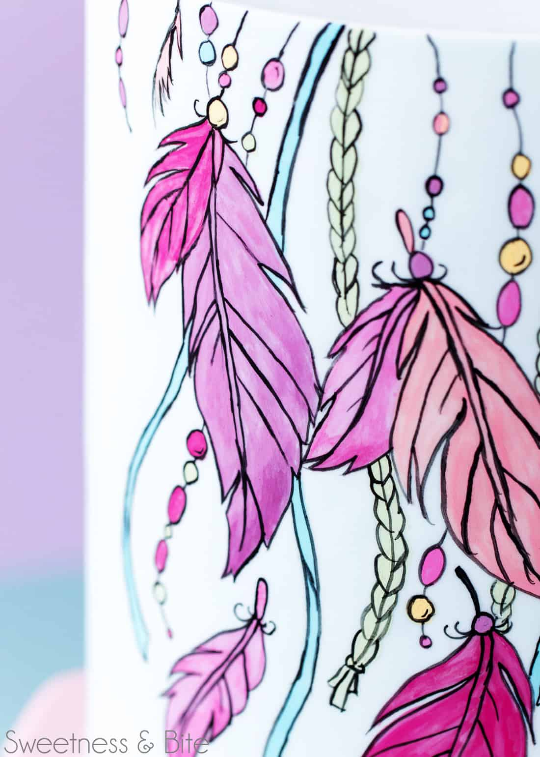 Close up image of the painted and outlined design around front of the cake.