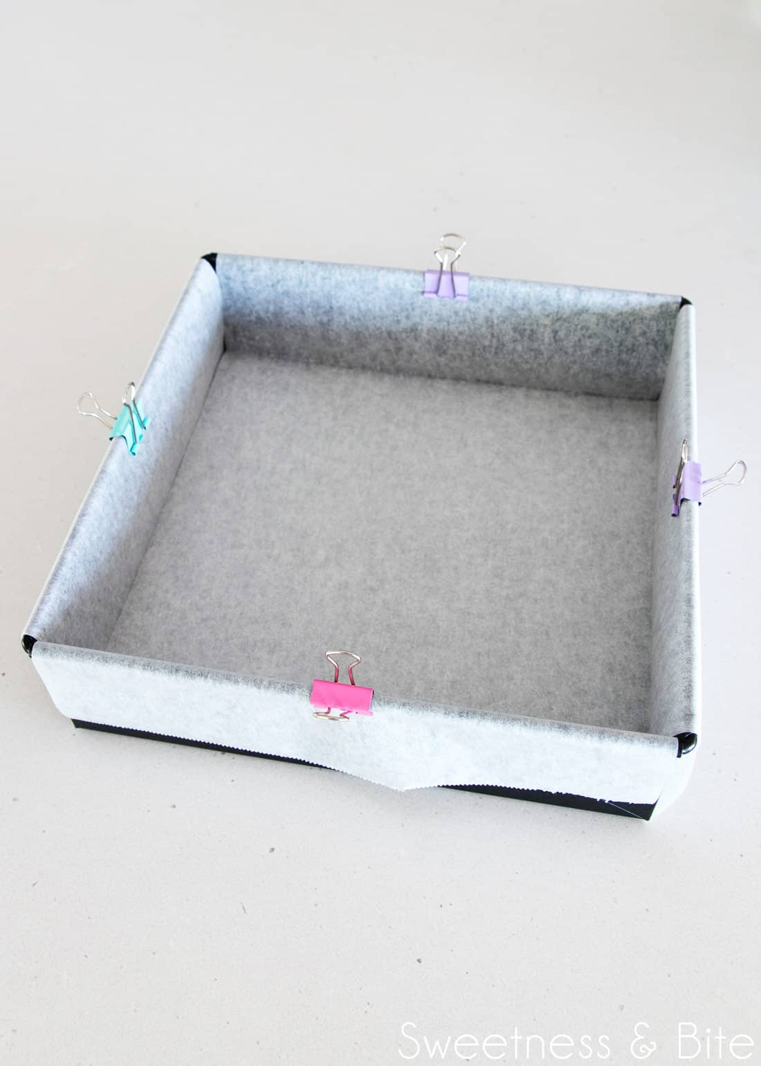 A dark metal square cake pan, with two strips of baking paper criss-crossed to line the pan, with coloured clips on each edge to hold the paper in place.