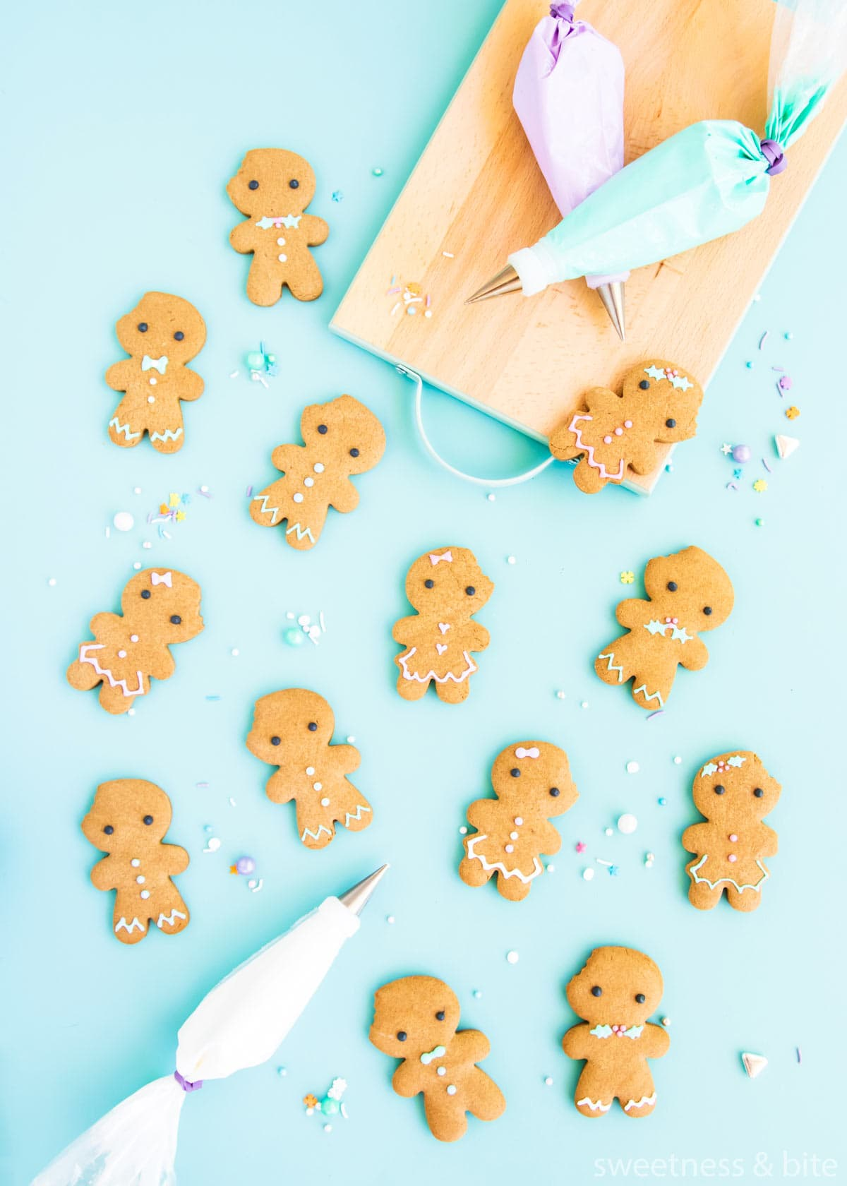 Gingerbread people cookies on a blue background, with pastel coloured royal icing in piping bags.