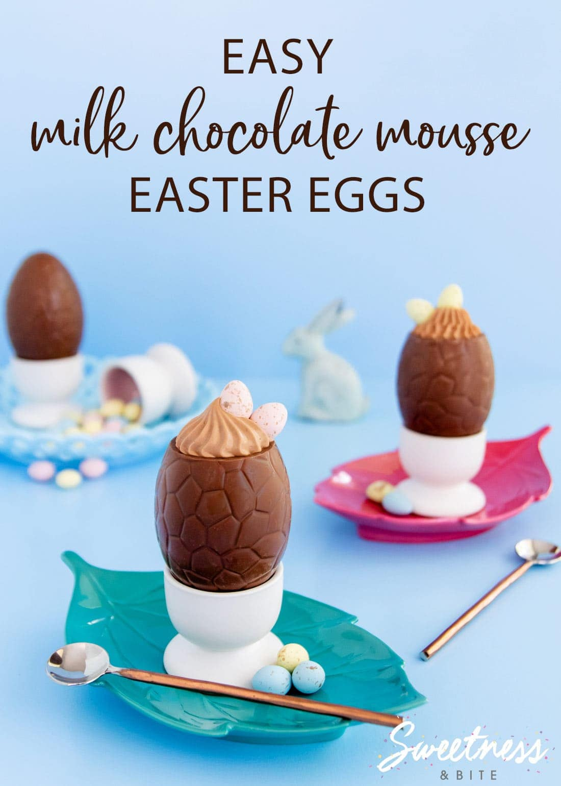 Milk chocolate mousse filled Easter eggs, sitting in egg cups on green and pink plates.