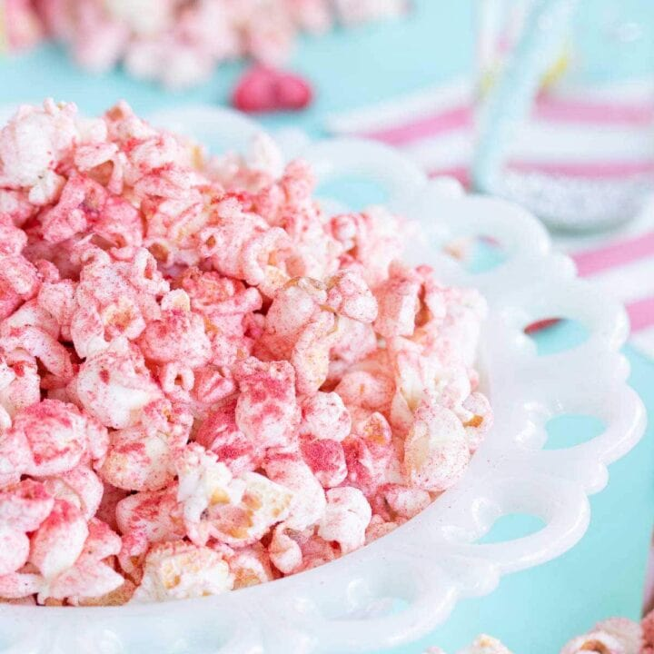 A white milk glass bowl full of fruit flavoured popcorn.