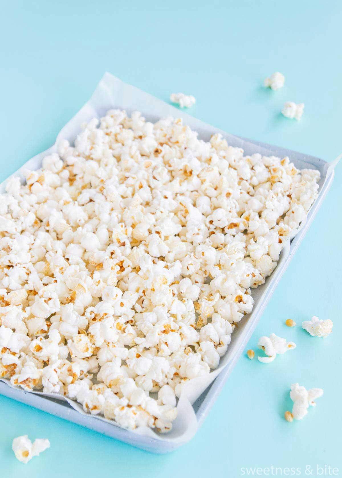 A tray of plain, popped popcorn on a blue background.