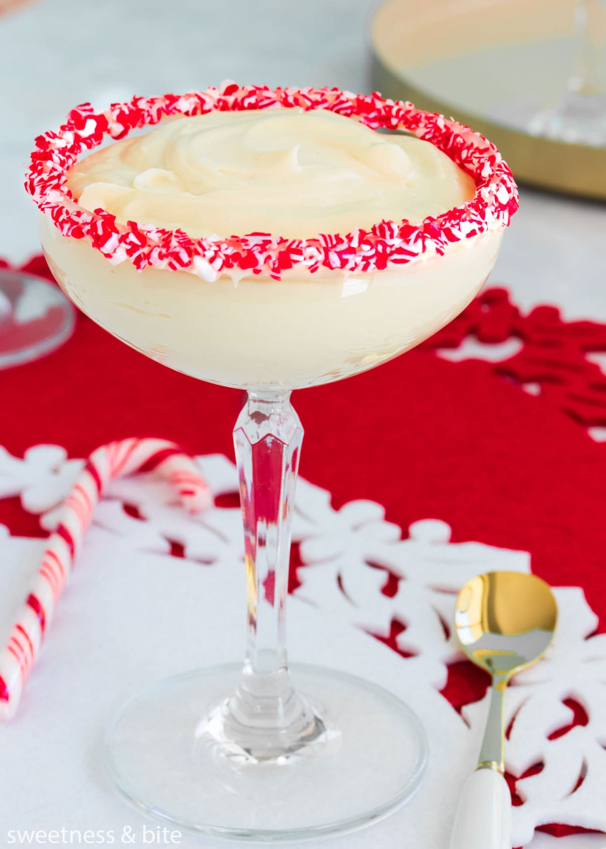 White chocolate peppermint mousse in a stemmed cocktail glass with crushed candy canes around the rim.