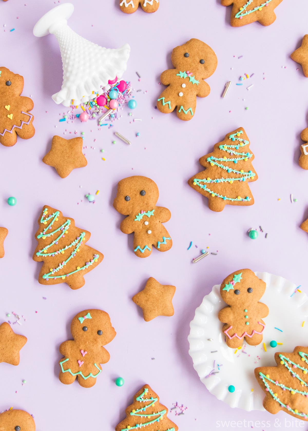 Gluten free gingerbread men and women with gingerbread Christmas tree and star cookies on a purple background, surrounded by pastel and metallic sprinkles.