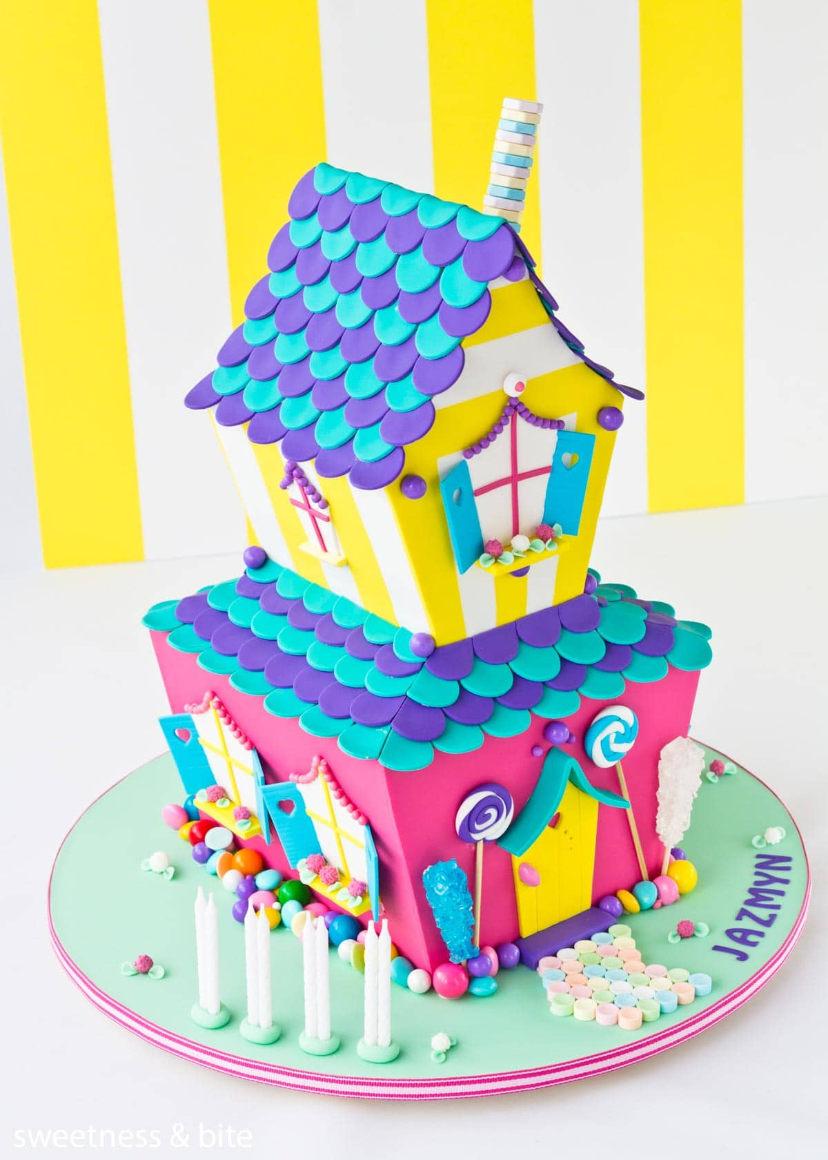 A brightly coloured two tier candy house cake.
