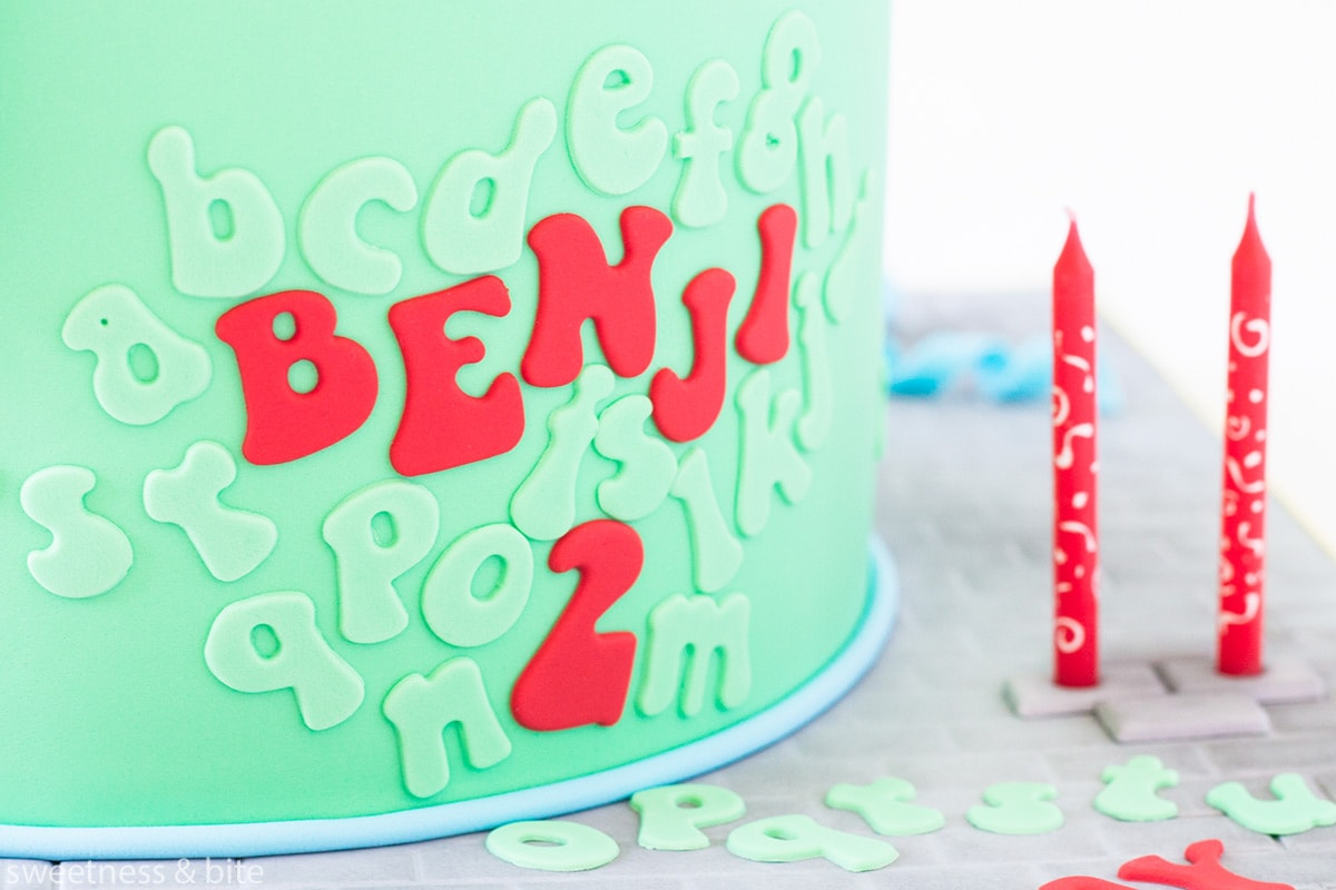 A bright green cake with red and green lettering attached to the front. Text reads: