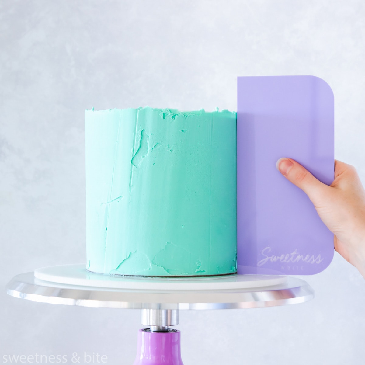 A cake being ganached with teal ganache using a purple scraper