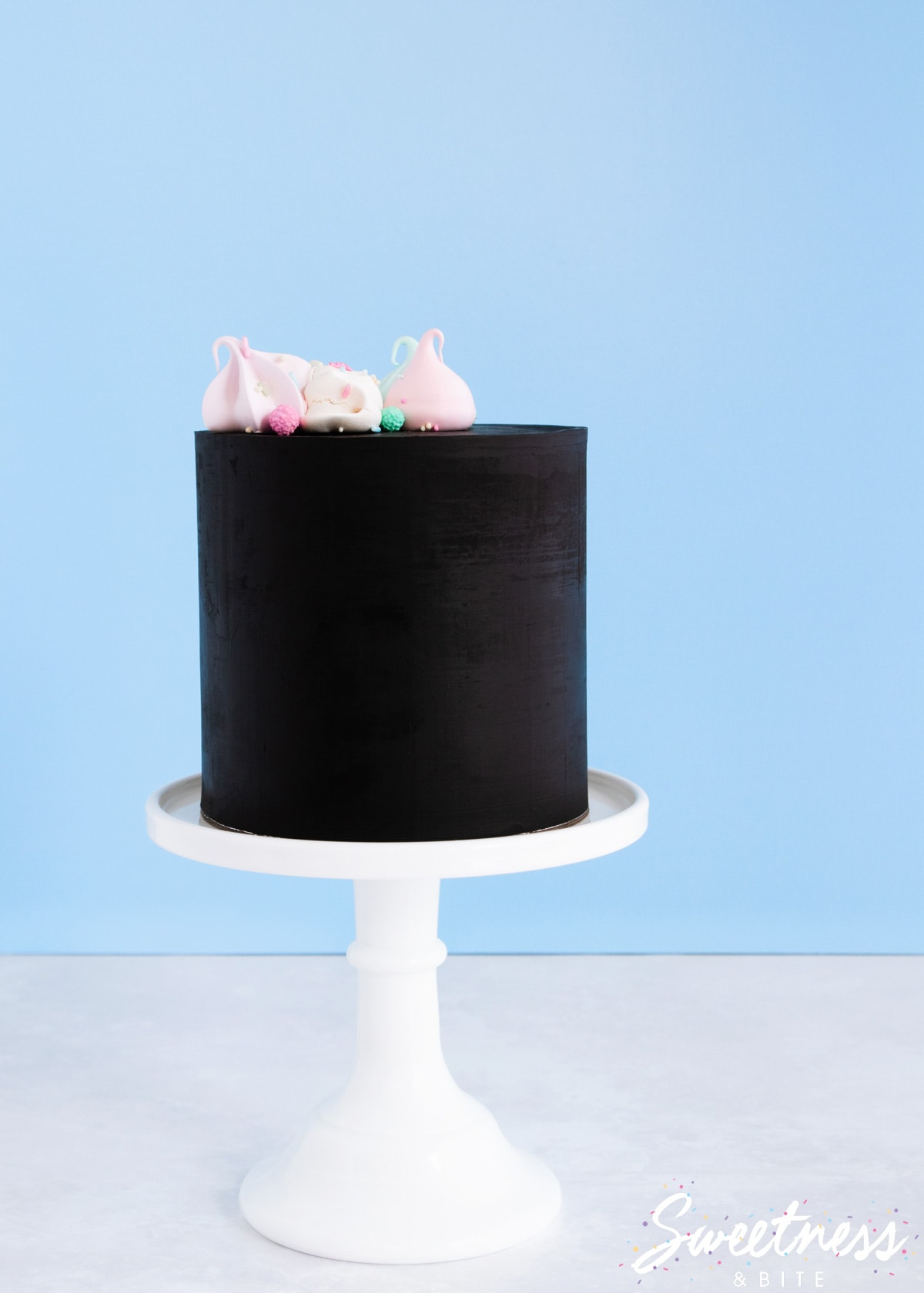 A cake covered in black chocolate ganache, on a white cake stand, topped with pastel meringues.