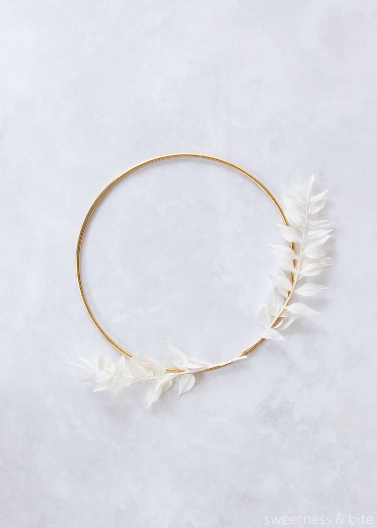 Two pieces of white ruscus tied to the hoop with clear thread.