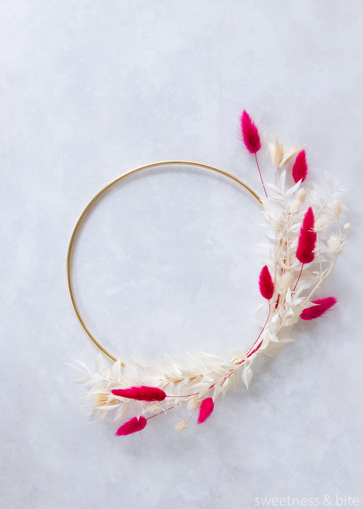 The two pieces of ruscus tied in place in the middle of the hoop.