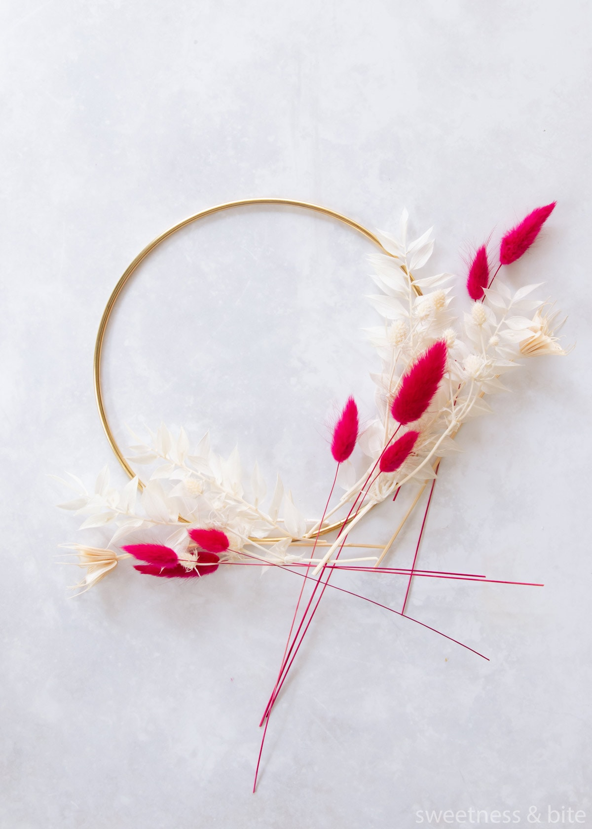 A gold hoop with white and pink preserved flowers and foliage arranged in a rough design.