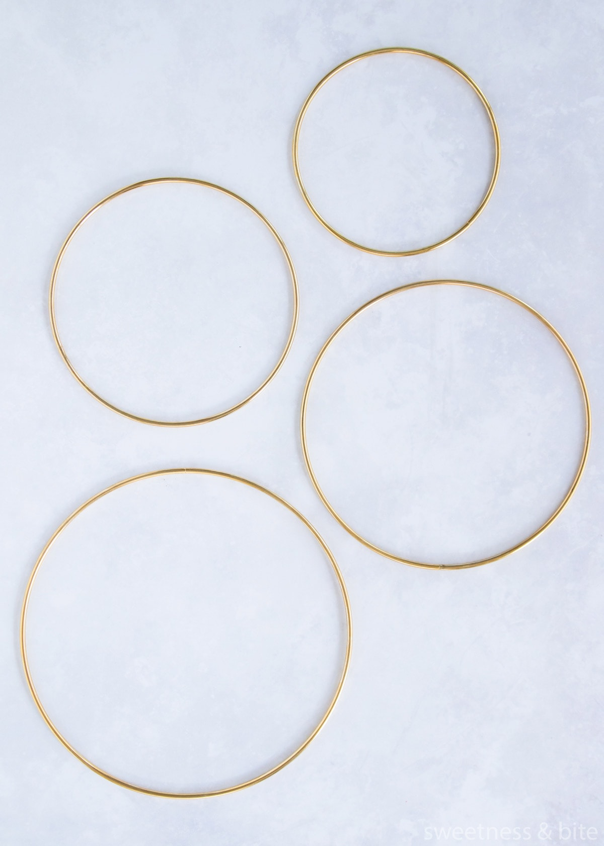Four gold coloured metal craft hoops of varying sizes.