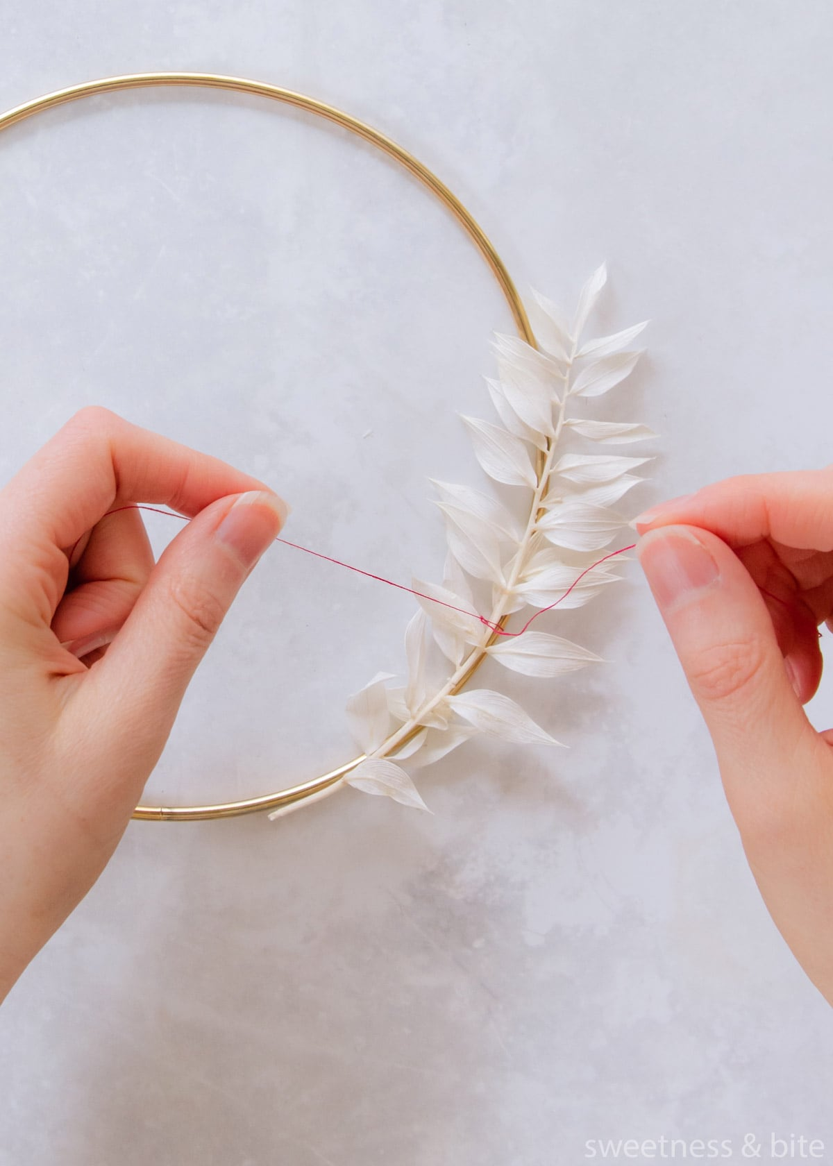 A stem of white ruscus leaved being tied to the hoop with pink thread.