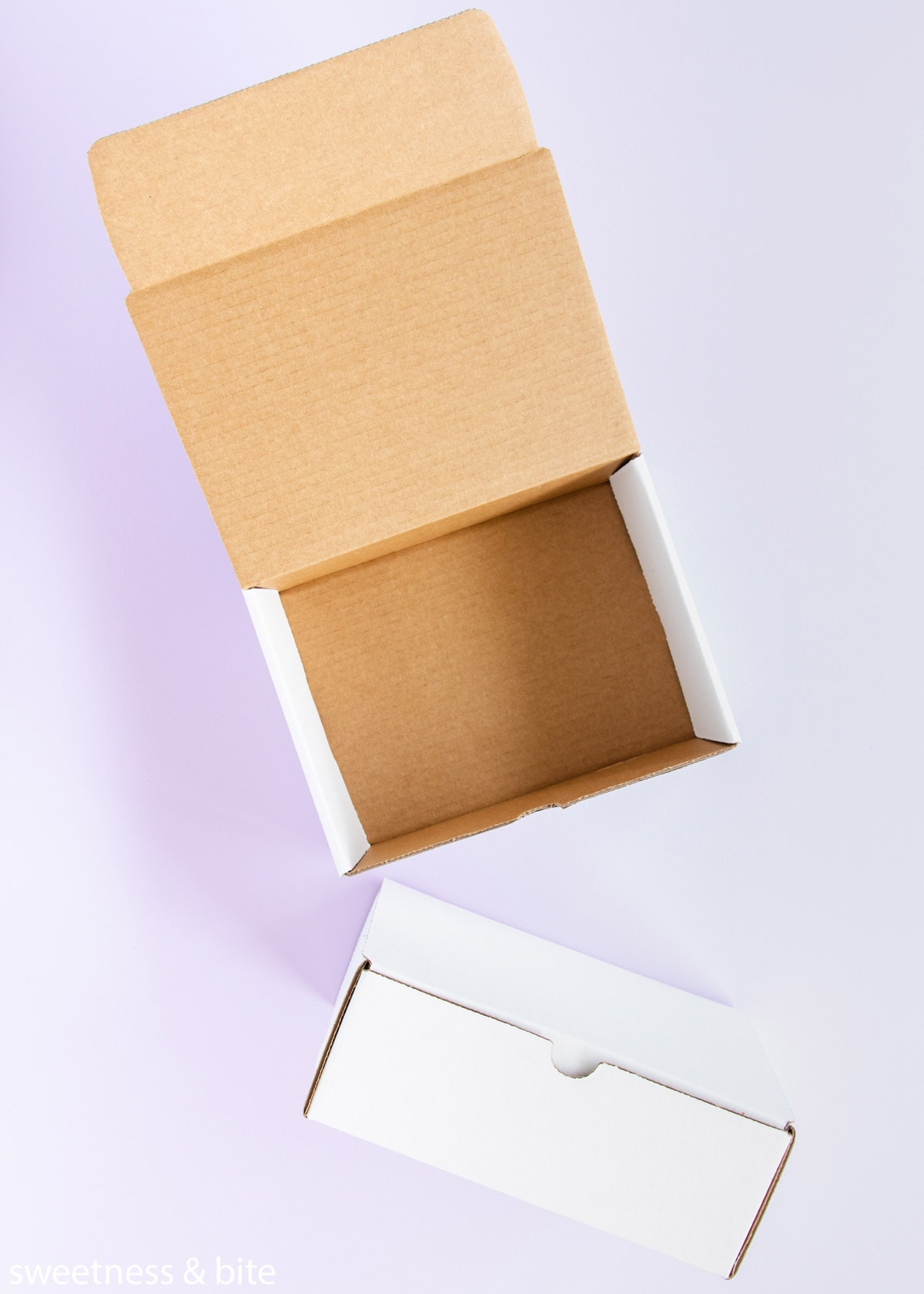 Two small white hinged-lid cardboard boxes.