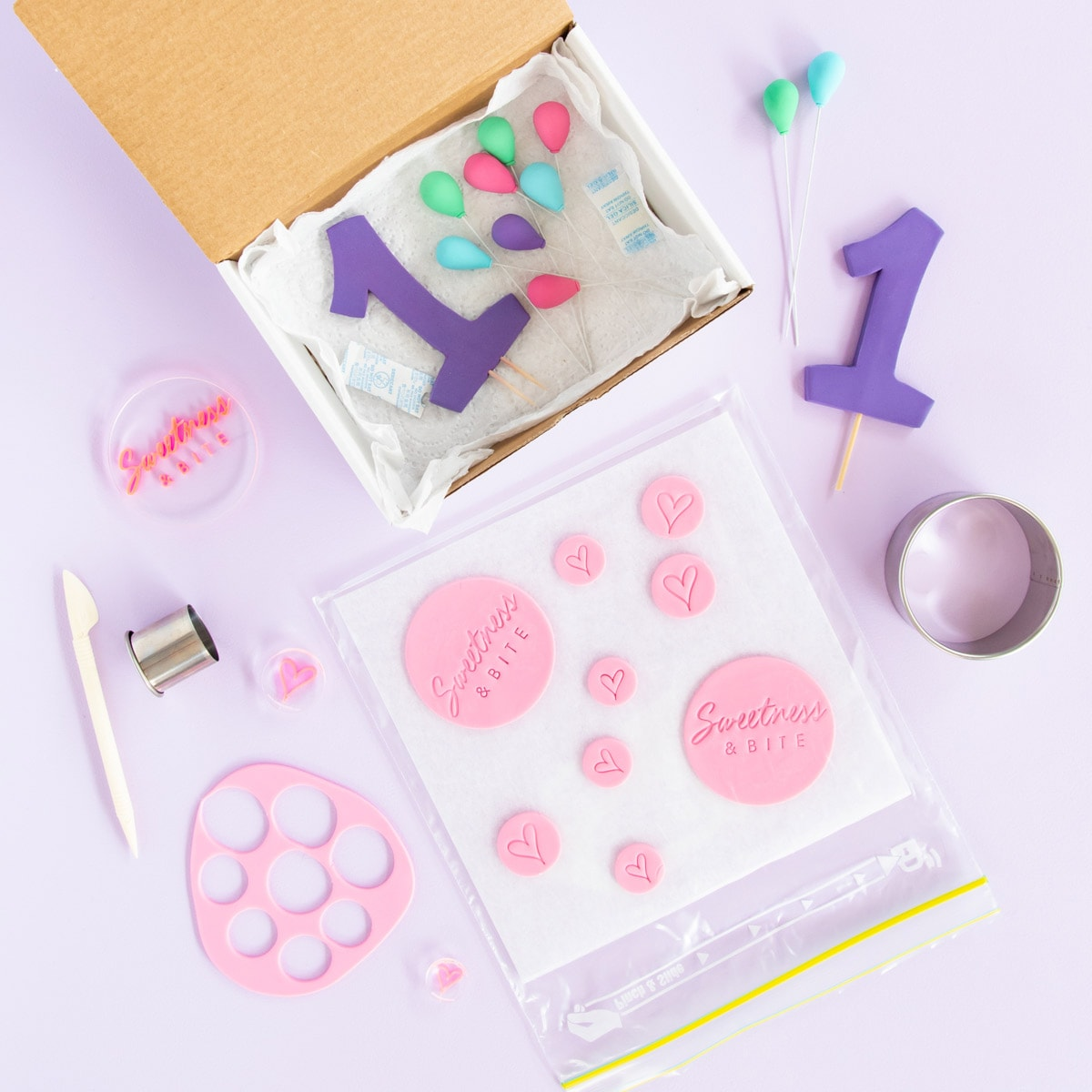 Fondant and gumpaste cake decorations in a box and in a resealable plastic bag.