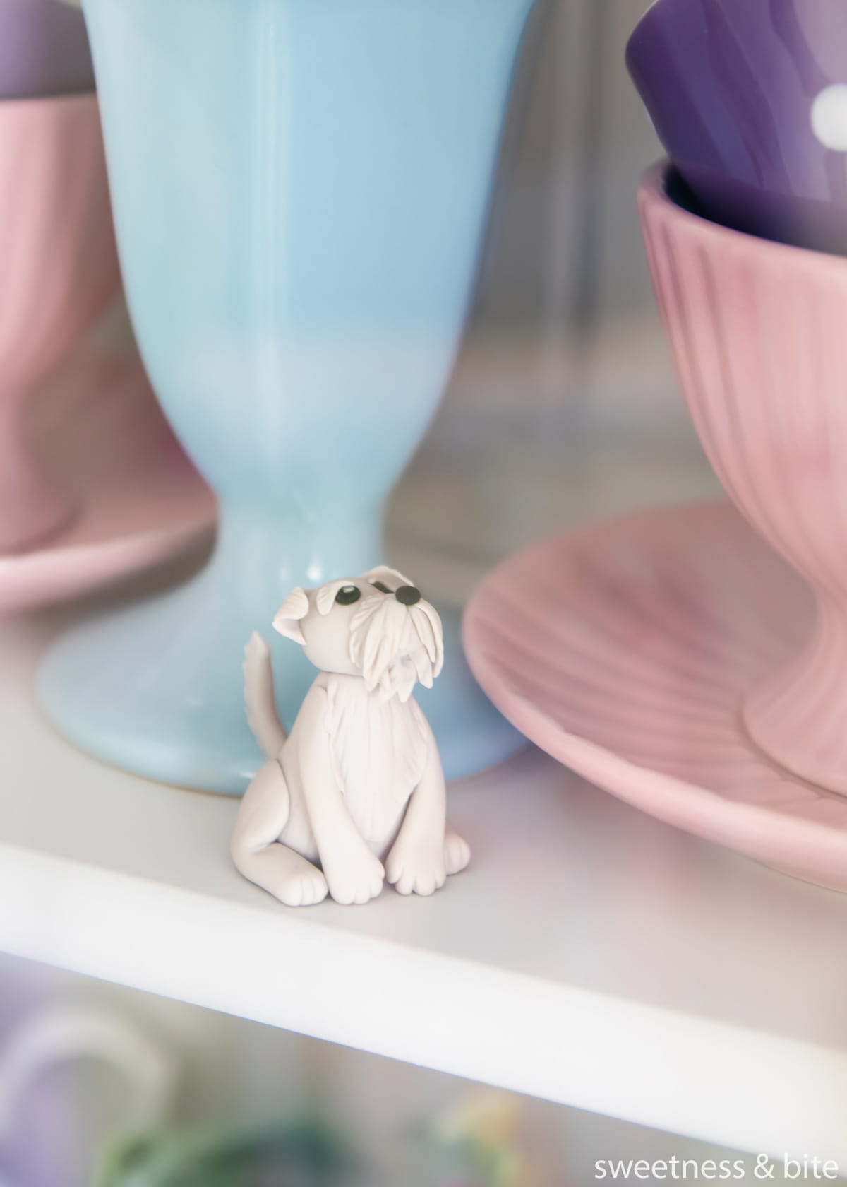 A small grey dog gumpaste cake topper being stored in a glass-door cabinet.