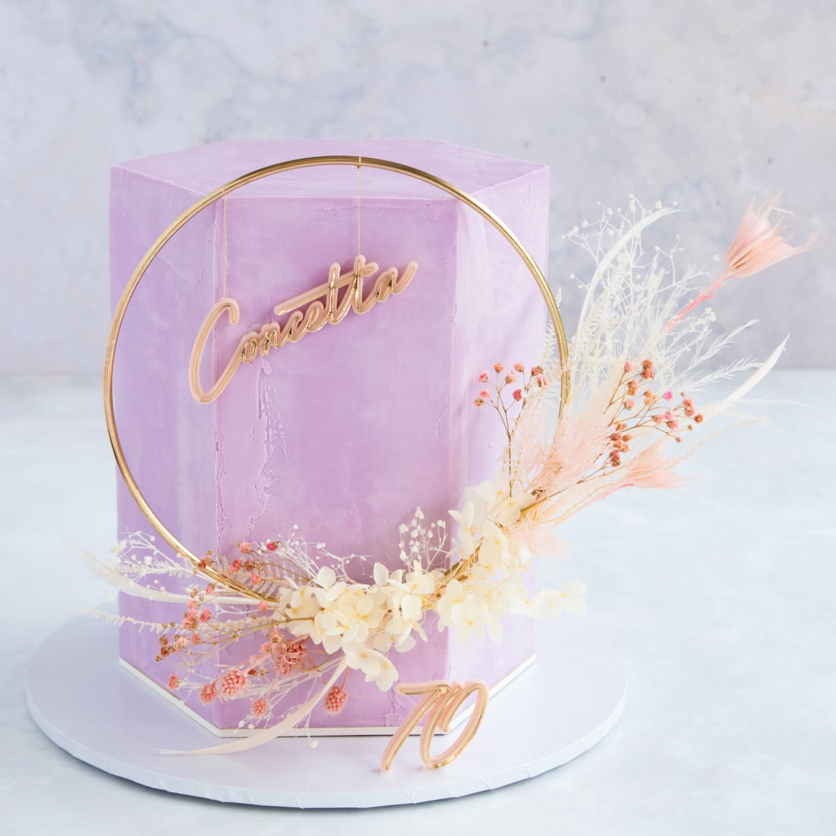A tall hexagon shaped cake covered in lilac ganache, with a pink and white floral cake topper.